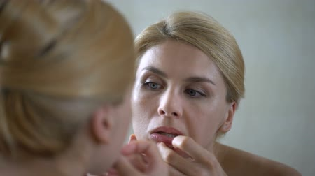 dermatologia : Insecure pretty lady popping pimple on skin, scrutinizing her mirror reflection