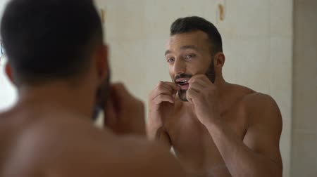 escovação : Male in bathroom brushes teeth with dental floss, tooth diseases prevention