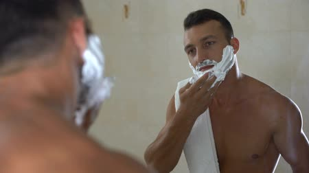 shaving foam : Brutal male showing razor and applying shaving cream to face and beard, grooming