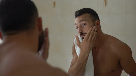 chafe : Man applying aftershave lotion to face in bathroom, prevention of skin dryness