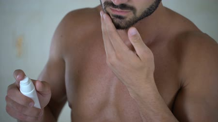 fryzura : Male applying lotion on beard to stimulate growth of facial hair, cosmetics Wideo