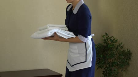 hotel suite : Smiling maid offering client white towels, impeccable service in five star hotel