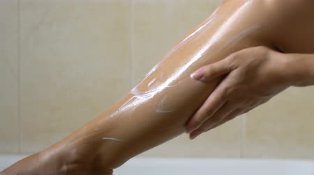 手順 : Woman applying lotion after waxing legs in bathroom, hair removal and skin care