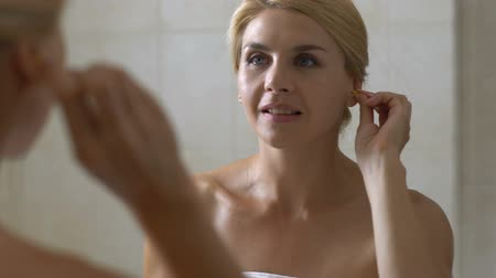衛生的な : Woman using cotton swab to clean her ears in bathroom, ear hygiene, healthcare