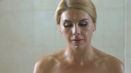 pleťová voda : Woman applying anti-aging lotion on face in bathroom, cosmetics and skin care