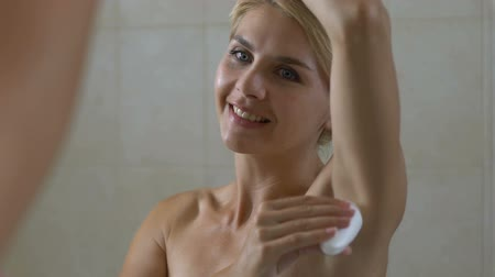dezodorant : Woman applying deodorant on armpit in bathroom, skin care and everyday hygiene Wideo