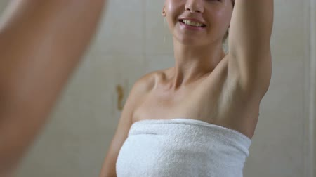 perfumy : Happy woman checking skin on armpit, good depilation, hygiene and healthcare