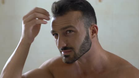 quebradiço : Unhappy man checking brittle hair in front of mirror in bathroom, dandruff Stock Footage