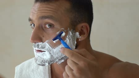 剃る : Man shaving face in front of mirror in bathroom in morning, everyday routine
