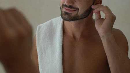 cotidiano : Bearded man using cotton swab to clean his ears in bathroom, ear hygiene, health
