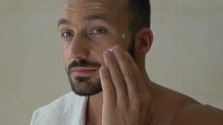только один человек : Man applying cream on his face in front of mirror in bathroom, cosmetics for men