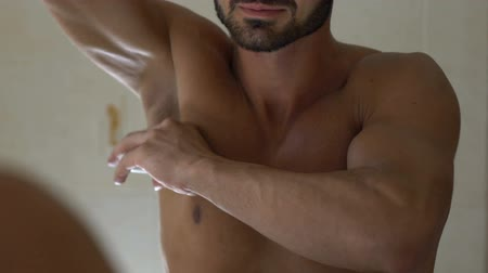 oksel : Man applying deodorant on armpit in bathroom, skin care and everyday hygiene Stockvideo