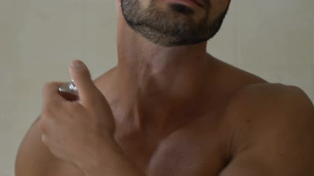 kolínská voda : Bearded man applying perfume on neck in bathroom, special fragrance for men