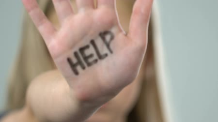 humiliation : Help message on little girl hand, school bullying victim, abuse awareness