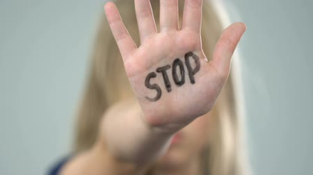 humiliation : Scared young girl showing stop sign, domestic violence victim, abuse awareness