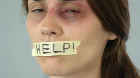 cativeiro : Help message on taped mouth of bruised woman, helpless silent abuse victim