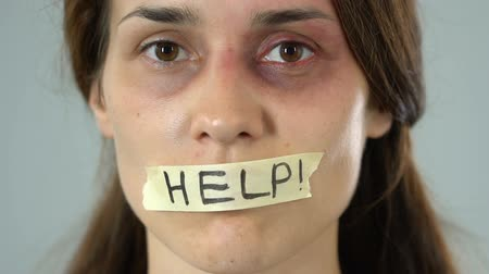 tyranny : Help word on taped mouth of bruised woman, intimidated abuse and violence victim Stock Footage