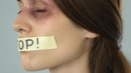 tyranny : Stop message on taped mouth of bruised woman, helpless silent abuse victim Stock Footage
