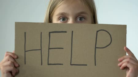 хулиган : Help word on poster in hands of scared little girl, bullying abuse awareness