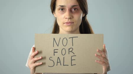 tehetetlen : Not for sale text on poster in bruised woman hands, problem awareness concept