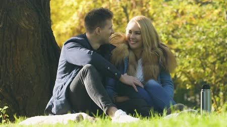 warms : Happy couple having picnic in autumn forest, man kissing lady, romantic date