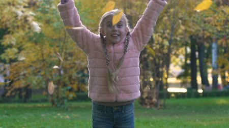 pigtailler : Happy child with pigtails throwing up autumn leaves, joyful childhood time Stok Video