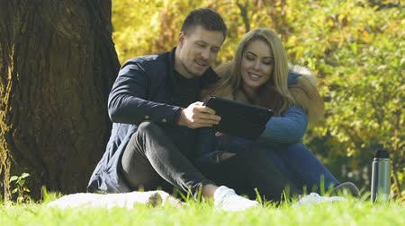 тачпад : Young couple using tablet outdoor, wireless internet, shopping or booking online Стоковые видеозаписи