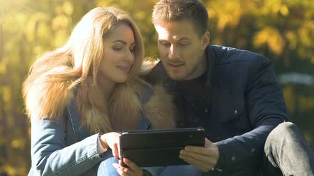 booking : Happy couple using tablet, sitting in autumn park, shopping or choosing tour Stock Footage