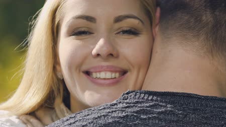 liefdevol : Happy woman hugging beloved man, looking at camera, happy marriage, closeup