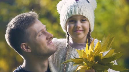 bochecha : Girl holding bouquet of autumn leaves, father kissing daughter on cheek, closeup Stock Footage