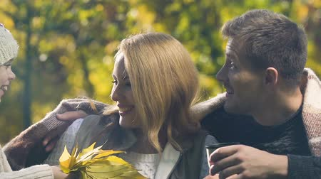 warming up : Closeup of couple talking in park, daughter gives autumn leaves, happy family