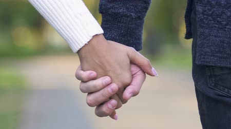 человеческая рука : Young couple holding hands and walking together, concept of support and trust Стоковые видеозаписи