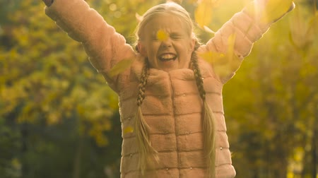 восхищенный : Cute girl in fur coat throwing up autumn leaves, carefree and happy childhood