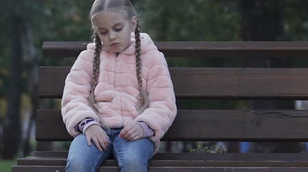 bully : Upset little girl sitting on bench in park, feels lonely, lack of communication Stock Footage