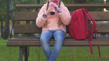 szomjúság : Schoolgirl drinking tea from thermal, snack in park after school, healthy food Stock mozgókép