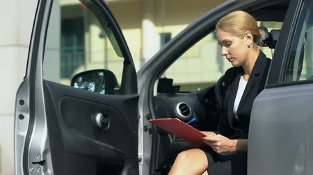 bérlet : Woman fills car rent insurance form, sitting in automobile, business trip