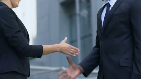 together trust : African american male and caucasian female shaking hands, profitable deal
