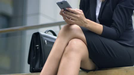 блог : Business lady sitting on bench, resting and checking e-mails on smartphone