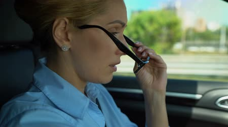engedély : Woman nervously puts on glasses while driving, worries about problems at work Stock mozgókép