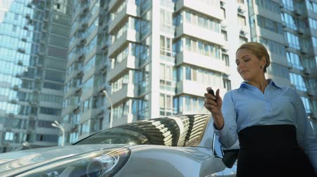 businesslady : Successful woman buys luxury auto, turns on car alarm, nod of approval, wealth