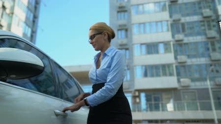 engedély : Businesswoman receives keys to luxury auto from dealer, car loan or purchase