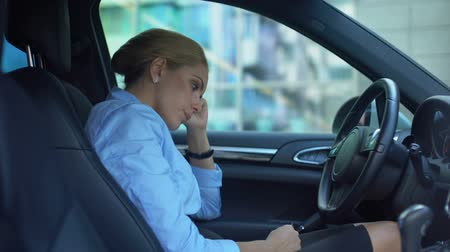 licenziamento : Frustrated businesswoman takes off glasses, sitting in car, upset with failure