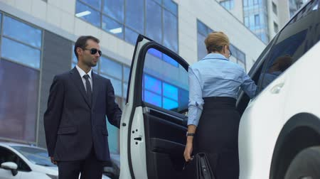político : Personal assistant of female politician opening car door to his boss, service