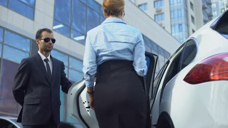 prestiž : Doorman of business centre opening car door to lady businesspeople accompaniment