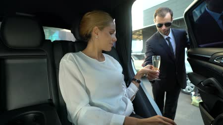 ulaşmak : Personal assistant giving glass of sparkling champagne to reach woman in car Stok Video