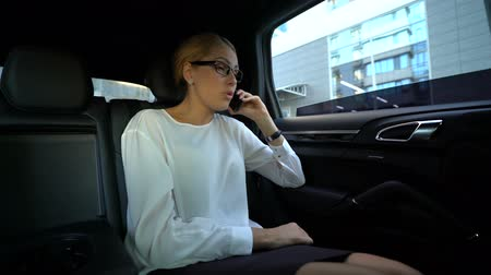 descontente : Business woman annoyed with conversation, throwing phone out of car window