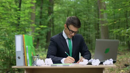 jó hangulatban : Creative young businessman writing down good ideas at desk in green forest