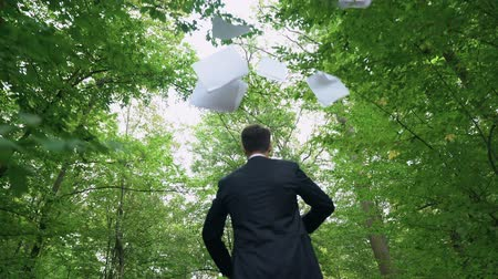 free throw : Businessman walking in forest and throwing away all papers, enjoying freedom