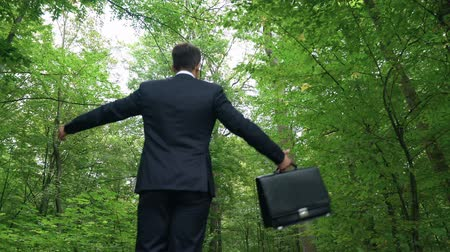 an : Manager with briefcase spreading arms and feeling energy of nature in green park