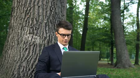 escaping : Inspired young businessman working on grass in park, escaping office routine